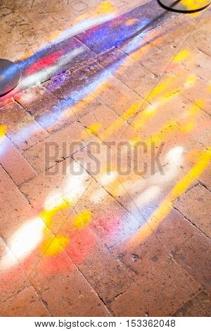 Colorful light spots on the the floor in church. Sunlight filtered through the stained glass window with game of light and shadow.
