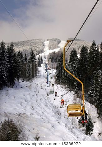 Snow landscape with cableway and skiers
