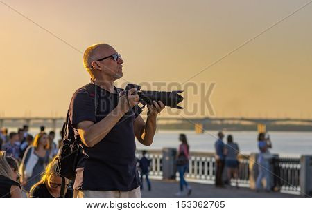 DNEPR UKRAINE - SEPTEMBER 10 2016:Mature photographer looking out people to shoot on Dnepr river embankment during City Day local activity in Dnepr, Ukraine at September 10, 2016