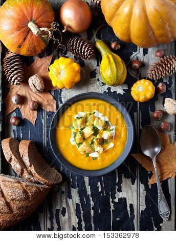Pumpkin and carrot soup with cream, croutons on creative old dark wooden background. For Thanksgiving, halloween. Copy space. Top view. Composition of autumn vegetables.