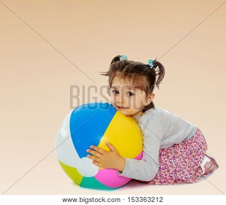 Cute little dark-haired girl with short pigtails on the head, hugging his big , inflatable, striped, vinyl ball.On a brown gradient background.