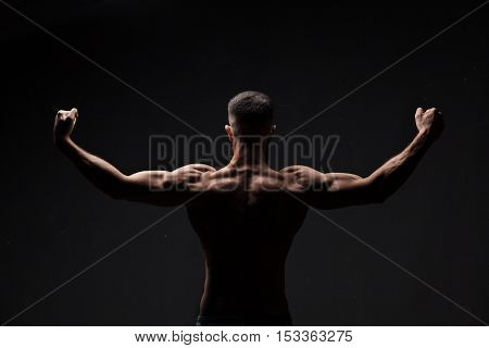 strong athletic mans back on dark grey gradient background