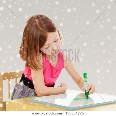Little girl schoolgirl sits and draws at the table, green marker on the white Board. Gray background with round white snowflakes.