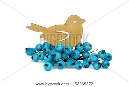 Little wooden bird is handmade and frozen berries isolation on a white background. Rustic decorations for Christmas.