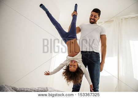 African american dad playing with his daughter.