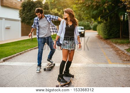 Teenage couple learning how to drive a long board.