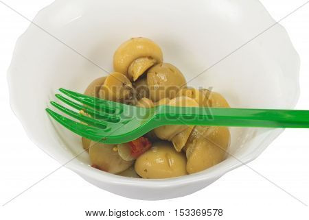Dish with marinated mushrooms on a white background