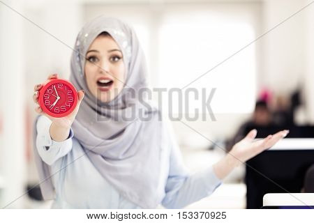 Businesswoman with clock being late for her deliverables.