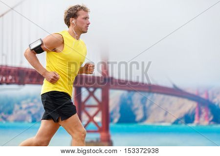 Athlete running man - male runner in San Francisco listening to music on smartphone. Sporty fit young man jogging by San Francisco Bay and Golden Gate Bridge. Jogger training with smart phone armband.