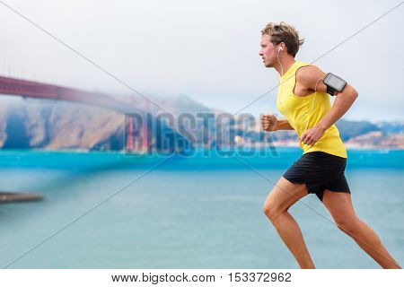 Runner man listening to music during run cardio workout. Running athlete using app on smartphone armband and earphones. Sporty fit young jogger jogging by San Francisco Bay and Golden Gate Bridge.