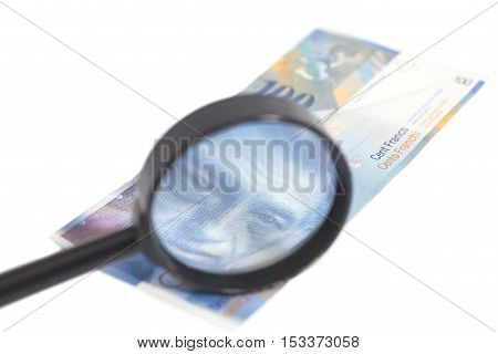 Swiss 100 Franc banknotes under magnifying glass isolated on white background