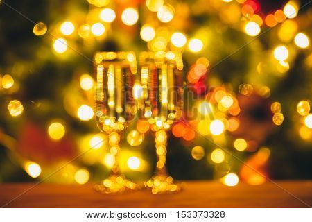 Beautiful Bokeh Two Glasses Of Champagne On Blurred Background With Christmas Tree. The Idea For Pos
