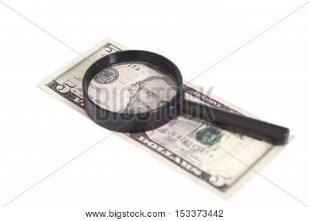 Five dollar bill with a magnifying glass isolated on white background