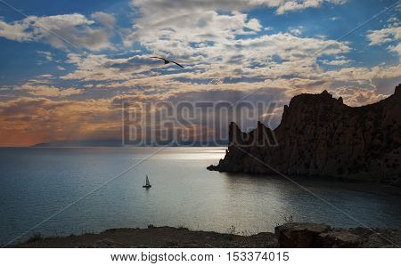 Evening landscape with sunset and clouds over a calm sea cliffs seagulls and a sailboat Crimea Novy Svet.