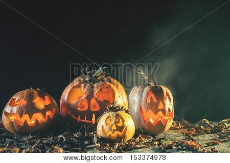 Halloween pumpkins at wood background. Carved scary faces of pumpkin. Night horror. October holiday. Pumpkin family. Holiday at October 31, 2016