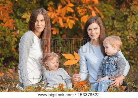 Alternative lesbian family with mothers, daughter and boy outdoor. Fall season. Protection rights. Healthy concept. Mothercare is most important in baby life
