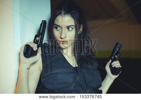 Model brunette girl with gun in a garage in attitude shoot, dressed in bulletproof vest