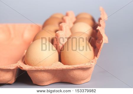 Cardboard egg box with brown eggs on gray background