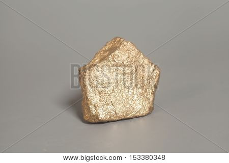 Golden nugget isolated on a gray background