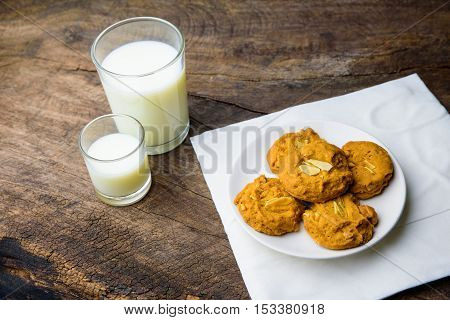 whole wheat almond cookies with a glass of milk and more cookies on old wooden table with warm light background.