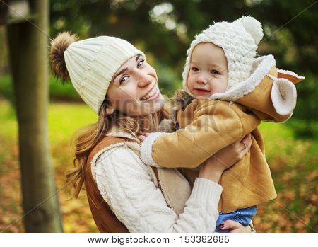 happy mother and her baby in the autumn park