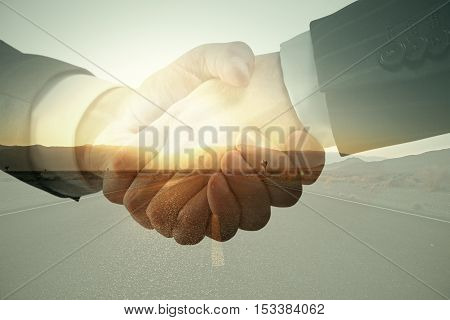 Closeup of handshake on road with sunlight background. Partnership concept. Double exposure