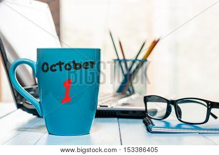 October 1st. Day 1 of month. Calendar on cup morning coffee or tea teacher, student workplace background.