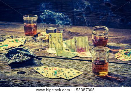 Vodka, Cigarettes And Cards On Vintage Table For Illegal Poker