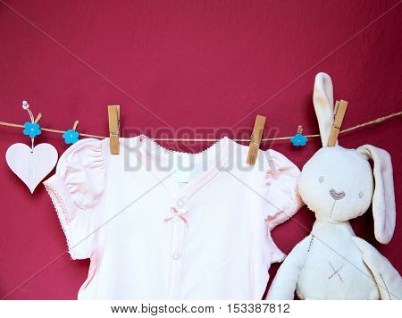 Baby child clothes and goods and toy hanging on clothespins on the clothesline on a textured wall background with copy space. Baby concept background.