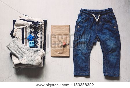 Autumn or winter children's outfit clothes. Top view fashion trendy look of baby clothes with greeting card and accessories for the fall or winter.
