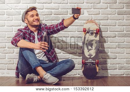 Stylish teenage boy in casual clothes and cap is doing selfie using a phone and smiling while sitting on the floor near skateboard on white brick wall background