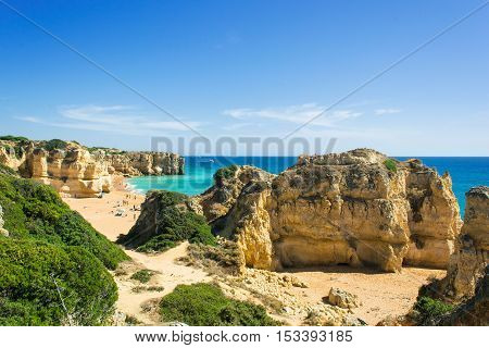 a view of beautiful sandy beach Pria do Castelo with cliff and rock formation in Albufeira Algarve region Portugal