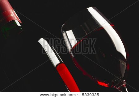 Glass and bottle of red wine on black