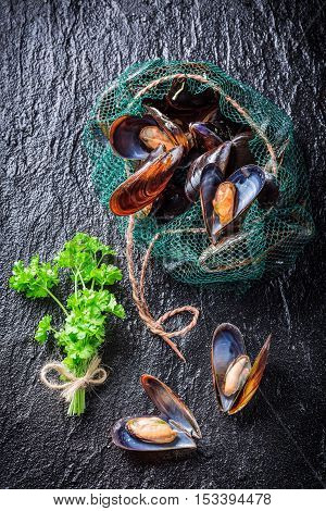 Fresh mussels on ice with ingredients on old wooden table