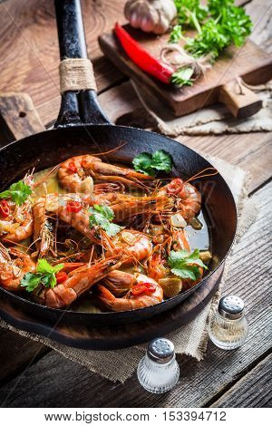 Tasty shrimps served on hot pan on old wooden table