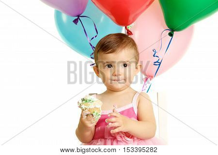 Cute One Year Old Baby Girl Celebrating her birthday with balloons and a cupcake.  Shot on a white background