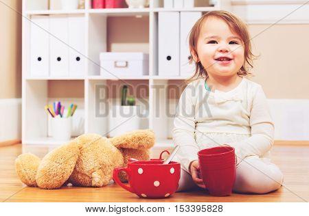 Toddler Girl Having Tea Time With Her Teddy Bear