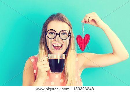Woman Drinking Coffee With Heart Cushion