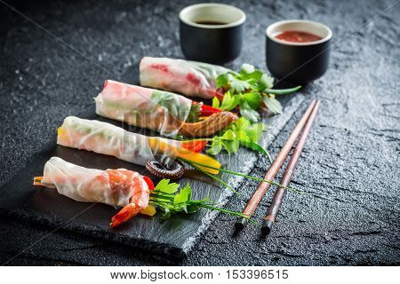 Enjoy your spring rolls with seafood on black rock
