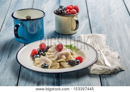 Dumplings with berry fruits and cream on old wooden table
