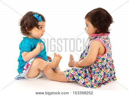 Two cute baby girls sitting and staring at each other on a white background