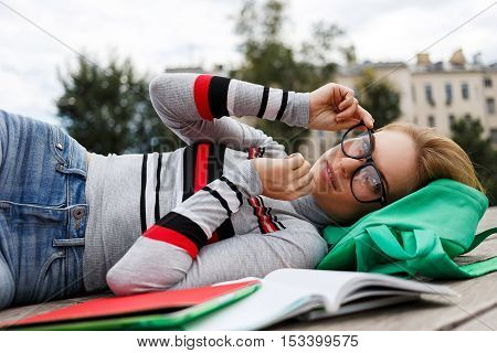 Young woman in glasses lay on wooden floor of building in background