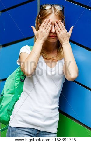 Girl closed her eyes hands amid striped wall.