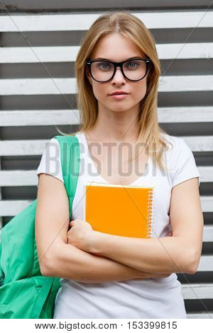 Girl in glasses folded arms stands at wooden fence