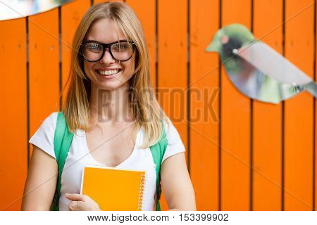 Cheerful girl in glasses amid Orange fence with birds