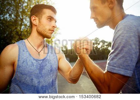 Portrait of two handsome athlete men handshake outdoors on summer day. Focused on hands. Natural sunflare.