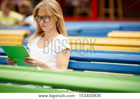 Blonde with glasses reading book among the benches in summer