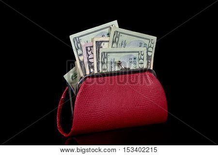 American money in red purse isolated on black