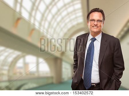 Happy Businessman Standing Inside Corporate Building.