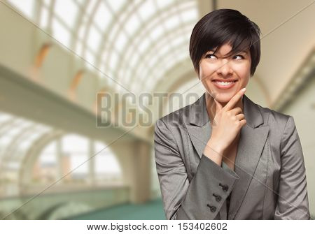 Pretty Businesswoman Standing Inside Corporate Building Looking To The Side.